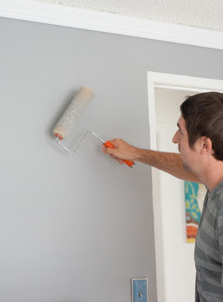 Man painting the wall with a roller