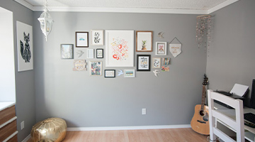 Newly painted wall with several pieces of framed artwork