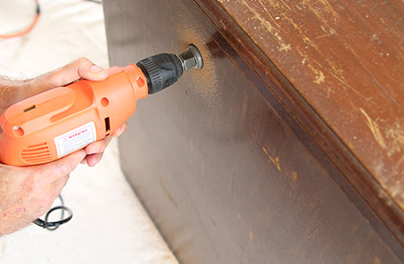 Using an electric drill with a keyhole bit to drill a hole for electric cords