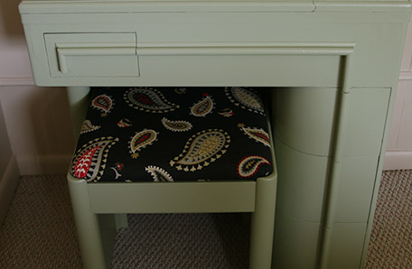 Close-up of the desk and stool, with new paint and paisley upholstery