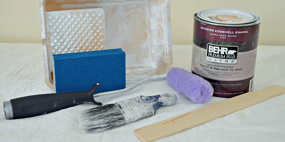 Paint brush, roller, tray, sanding sponge, and a quart of Behr paint