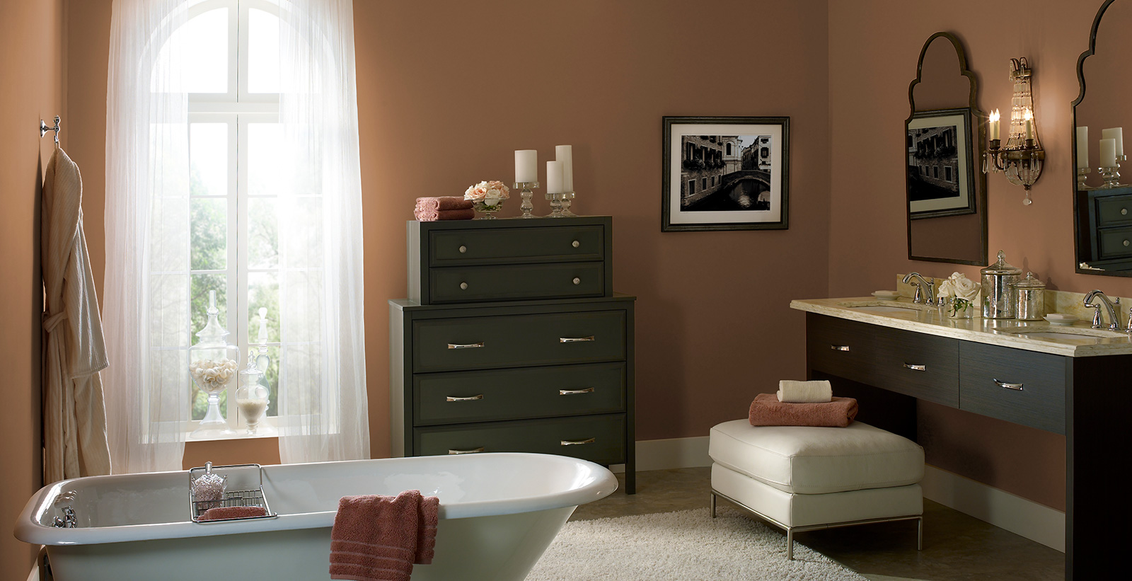 Modish themed bathroom with orange walls, white trim, and dark wooden dresser and sink.
