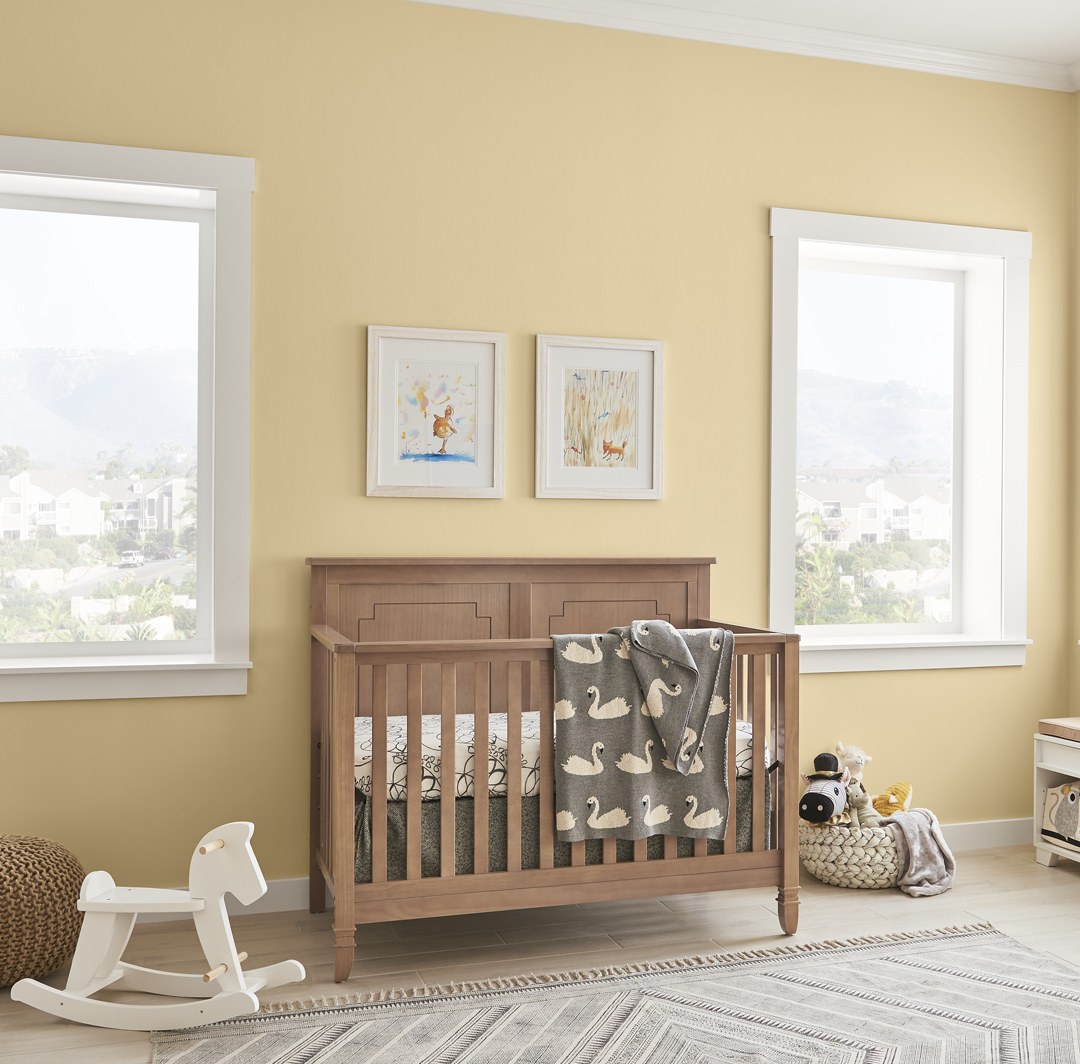 Inspirational youth nursery room small image with yellow wall and white trim, brown wooden crib with white rocking horse.