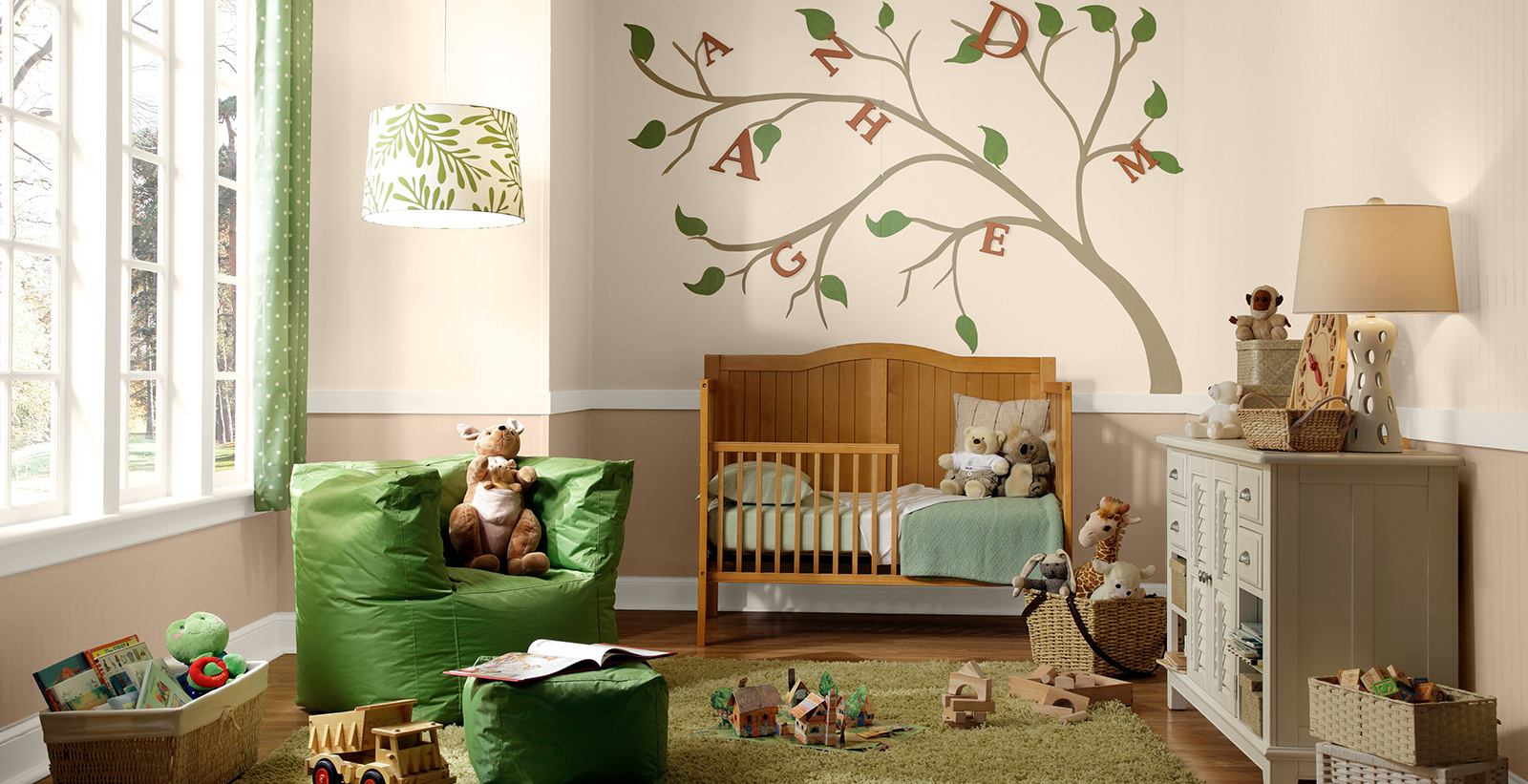 Relaxed and calming styled youth nursery room with light brown walls, white on the trim, wooden toddler bed, and painted tree.
