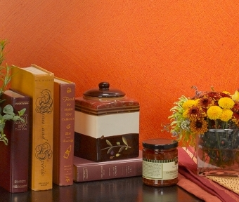 Decor items on a table beside an orange colored wall