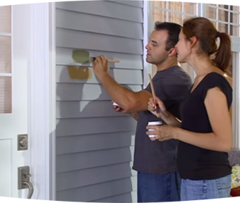A man and a woman testing paint colors on the outside of a house