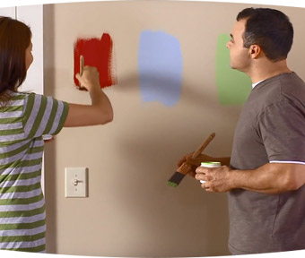 A man and a woman testing out different paint colors on the wall