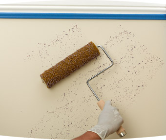 Person speckling the wall with a paint roller